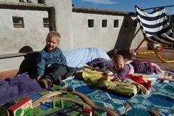 De kinderen spelen in een winters zonnetje op het dakterras